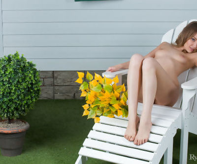 Sassy little Nikia spreads naked on a lawn chair in the summer sunshine