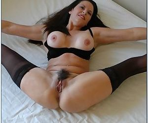 Mature vixen with hairy twat Selena Steele stripping and spreading her legs