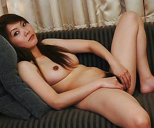 Asian chick undressing and exposing her juicy hairy twat in close up