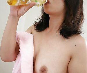 Naked asian MILF Naho Tajiri bends over to expose her shaggy gash