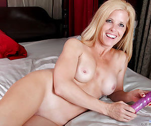 Busty mature vixen taking off her sheer lingerie and toying her cunt