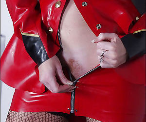 Redhead mature fetish lady in latex suit revealing her ample ass