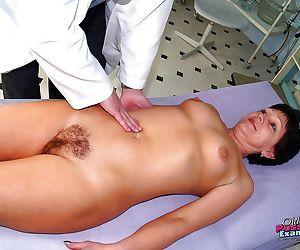 Hairy Mature bush dripping as it is spread wide for kinky exam at gyno