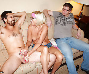 Lewd mature blondie in glasses milks a stiff cock with her skillful hands