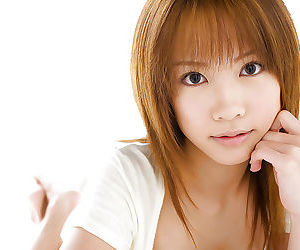 Asian teen cutie Reika Shina uncovering her titties and bushy cunt
