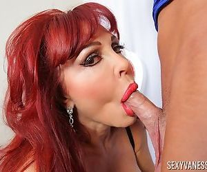 Older redhead Sexy Vanessa tugs on the nut sac while sucking cock