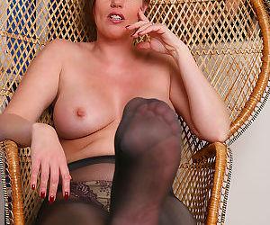 Sexy older brunette Holly Kiss peels black sheer pantyhose to tease nude