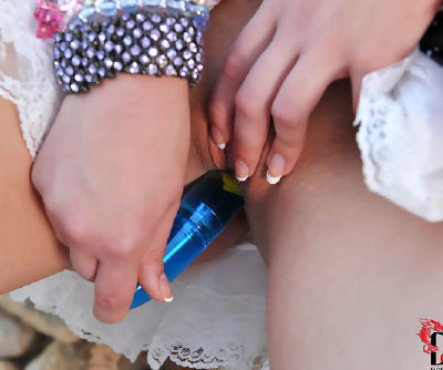 This shameless and petite teen in white panties is masturbating her cunt with toy outdoors