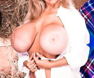 Famous pornstar Busty Dusty pours water over her mega tits in the stables