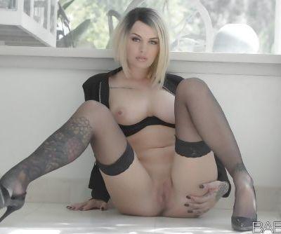 Stunning tattooed blonde Emma Mae modeling in black stockings
