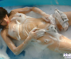 Seductive asian babe getting wet in her bikini and slipping it off - part 2