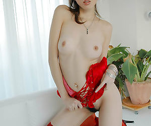 Seductive asian babe with tiny tits posing in red lingerie and stockings