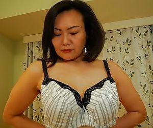 Asian MILF Kaoru Mitamura getting naked and demonstrating her juicy twat