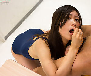 Slim Japanese chick jerks a cock until it blows jizz on her swimsuit clad ass