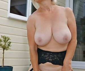Older blonde woman with large boobs masturbates on back patio in stockings