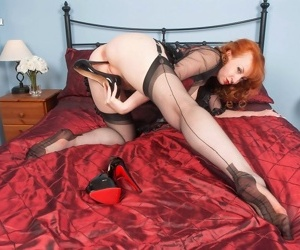 Mature redhead takes off her stiletto heels in nylons and garters