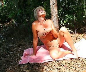 Blonde mature woman Tracy Lick baring nice tits & spreading naked in the woods