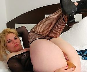 Mature blonde woman in fishnet stockings Bella B fucks herself with a dildo