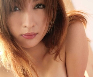 Japanese girl with reddish hair exposes small tits and bush during solo action