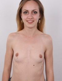 Thin female removes all of her clothes to stand naked as the day she was born