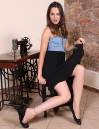 Fully clothed woman dangles a flat black shoe off her bare foot