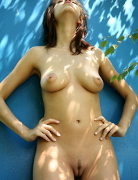 Naked brunette Eufrat shows perky tits and landing strip pussy in the garden