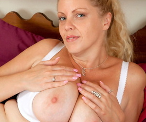 Mature amateur Teya plays with her huge all natural tits on her bed