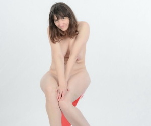 Ugly brunette mature with saggy tits poses naked in heels spreading long legs