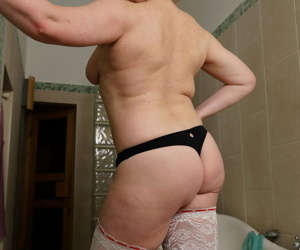 Older woman with a few extra kilos on her frame strips to stockings for a bath