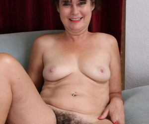 Horny mature woman removes her flower dress to toy her hairy beaver on the bed
