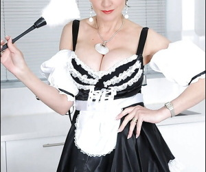Smiley mature fetish lady posing in sexy maid uniform and stockings