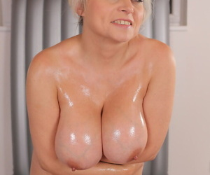 Horny mature Sindy Huga strips to oil her huge big tits & toy with dildo naked