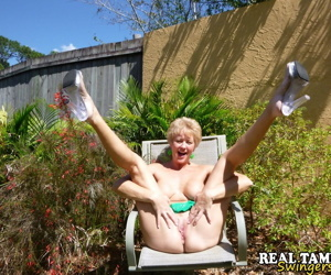 Mature lady takes off hr underwear to show her twat on a chair in backyard