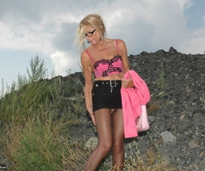 Tall blonde wanders around vacant land in crotchless hose and miniskirt