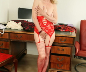 Mature lady Isabella Diana strips to fishnet stockings and lingerie on desk