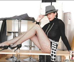 Fully clothed mature woman in fishnet pantyhose doing upskirt