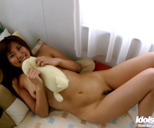 Alluring asian babe with hairy cooter stripping on the bed