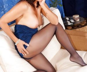Long legged mature Roni strips and masturbates through pantyhose