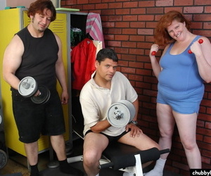 Fat older redhead Adrienne sucks and fucks two cocks in weight room