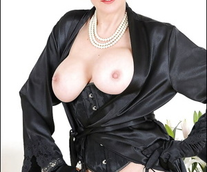 Mature brunette in glasses revealing her round boobs and inviting slit