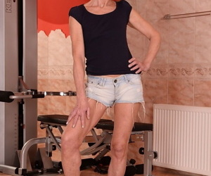 Redhead granny Katherin takes of her clothes to show her tits in the gym